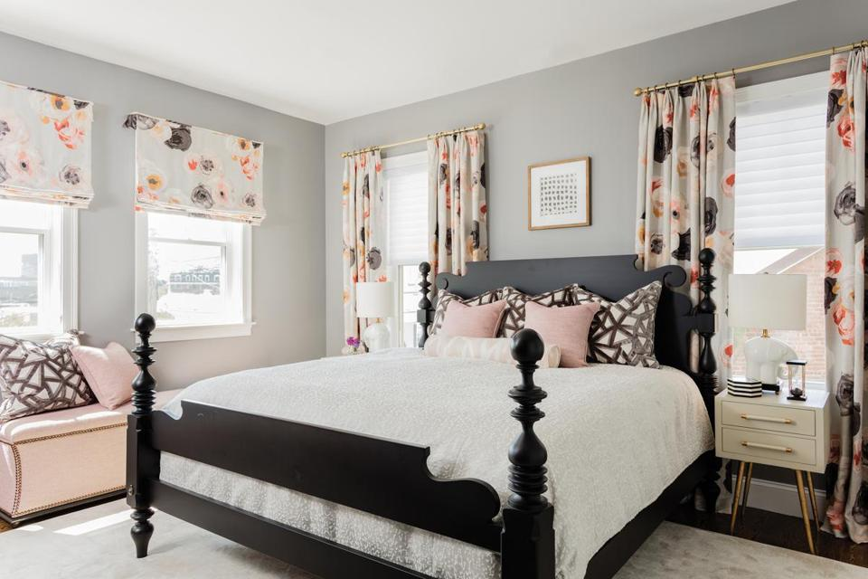 In the master bedroom (below), the drapes feature a pink floral motif to liven up the space's mostly gray and black scheme. The black four-poster bed pairs well with the neutral-toned Made Goods night stands, which have gold legs that add a little glam to the room. The storage ottoman was custom made by Kravet; the rug is by Stark.