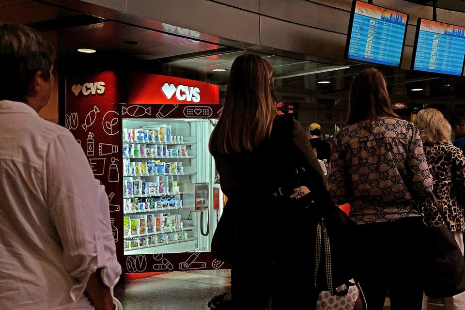 Passengers waited in line next to a CVS vending machine being set up at the South Station bus terminal.