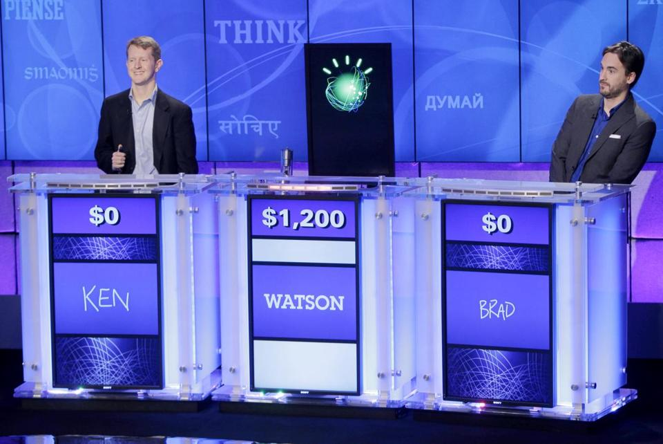 """Jeopardy!"" champions Ken Jennings (left) and Brad Rutter look on as Watson beats them to the buzzer in 2011."