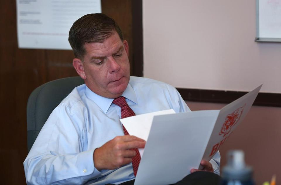 Boston Mayor Martin J. Walsh looked through an information packet on Brighton High School, as headmaster Robert Rametti gave an overview to visitors. The state declared Brighton High School underperforming during Walsh's tenure.