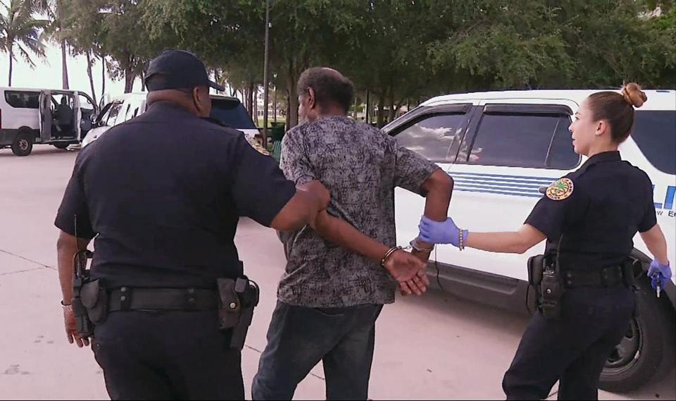 Officials in Miami detain a person who is homeless into shelters on Friday, ahead of powerful Hurricane Irma.