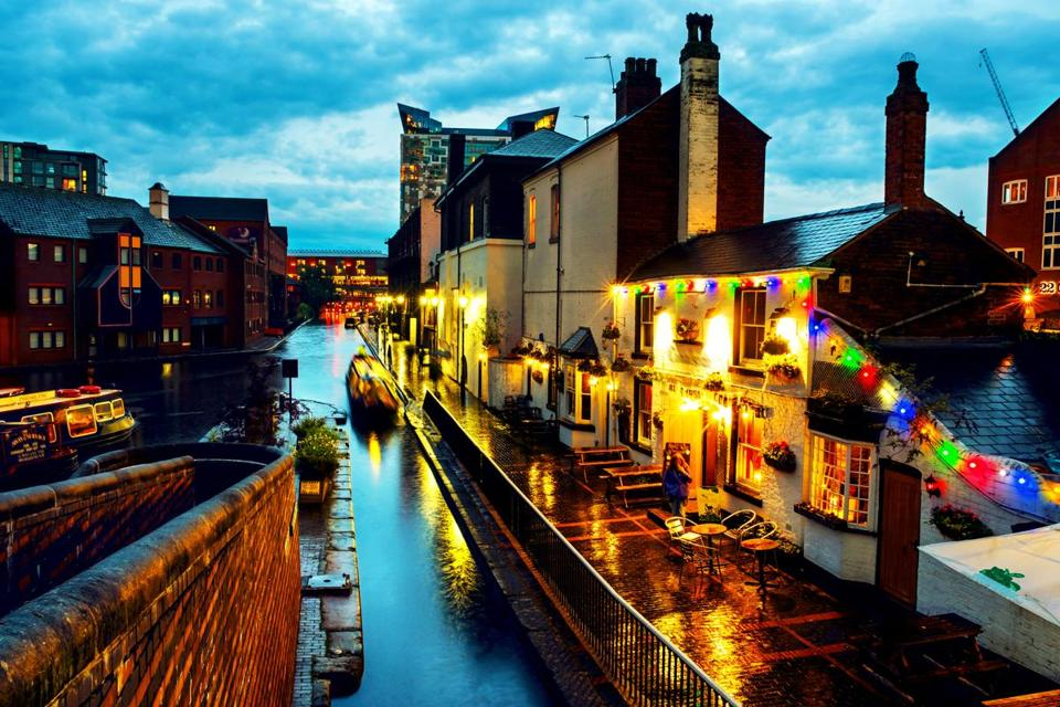 Birmingham, UK. People walking during the rain in the evening at famous Birmingham canal in UK