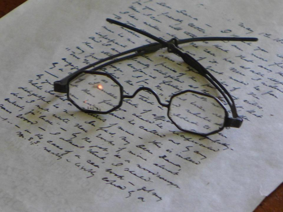 At Arrowhead, period glasses sit atop a sheaf of handwritten Melville pages.
