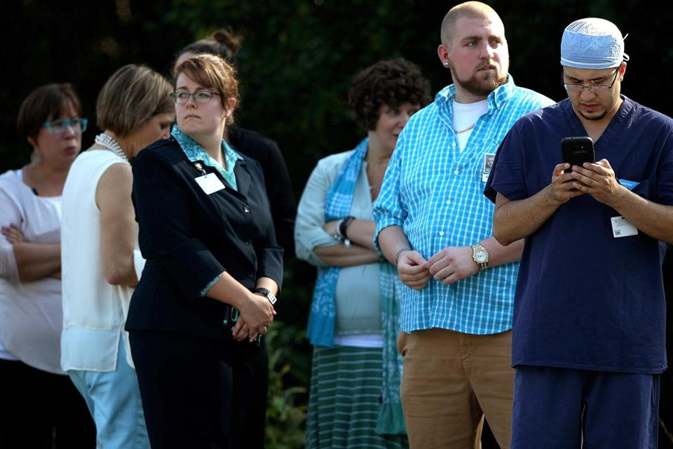 Lebanon, NH - 9/12/2017 - Manuel Bermudez, a surgical tech who works in the operating room at Dartmouth-Hitchcock Medical Center, at far right, and other employees wait for news after evacuating the hospital on reports of an active shooter. - (Barry Chin/Globe Staff), Section: Metro, Reporter: Unknown, Topic: 13lebanon, LOID:8.3.3712490102.
