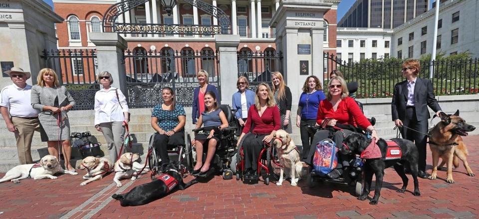A group including service dog teams stood outside the State House on Tuesday.