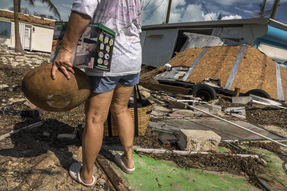 epa06203397 Sharon Noeller, resident of the Seabreeze mobile park, surveys the storm surge debris deposited in his backyard after Hurricane Irma struck the Florida Keys in Marathon in the Florida Keys, Florida, USA, 13 September 2017. Many areas remain under a dawn to dusk curfew. EPA/CRISTOBAL HERRERA