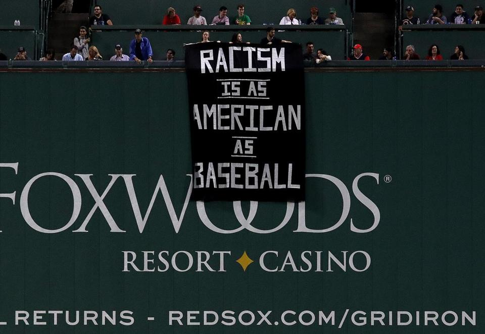 A banner is unfurled over the Green Monster during the fourth inning.