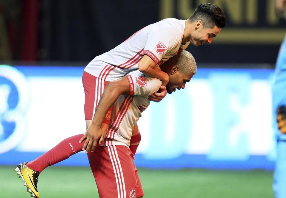 Atlanta United's Miguel Almiron jumps onto Josef Martinez after Martinez scored on a penalty kick against the New England Revolution during an MLS soccer match Wednesday, Sept. 13, 2017, in Atlanta. (Miguel Martinez/Atlanta Journal-Constitution via AP)