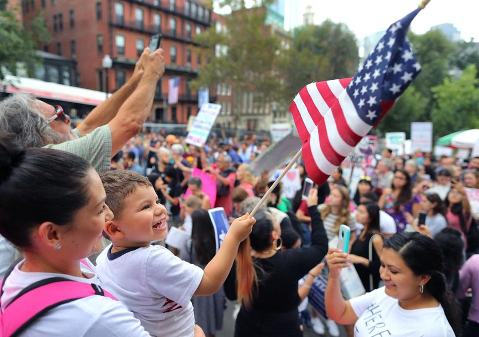 Boston-09/16/17- Rodrigo Valencia, 3, from Waltham waves a flag as he is help by his mother Vanessa as they joined hundreds of others who attended a DACA Rally on Boston Common followed by a march to the JFK building. John Tlumacki/Globe Staff(metro)