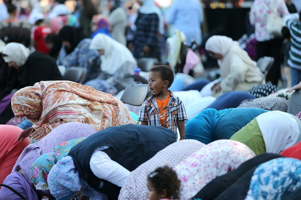 Mohammad Oubaha, 3, watched as his grandmother prayed at the festival.