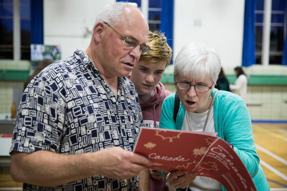 From left to right: Dan Taylor, Rebecca Taylor, 16, and Joan Smith, examined a EduCanada booklet at the EduCanada fair held at the International School of Boston.