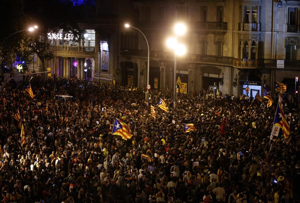A crowd of protestors gather outside the Catalan region's economy ministry building in Barcelona, Spain, Wednesday, Sept. 20, 2017. The Catalan regional government says that a top official in the management of the region's economic affairs has been arrested as a crackdown intensifies on preparations for a secession vote that Spanish authorities have suspended. (AP Photo/Manu Fernandez)
