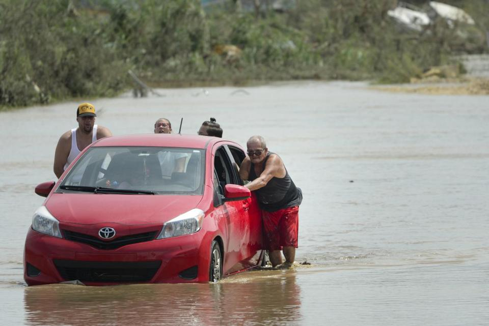 Residents pushed a car in a flooded road after the passing of Hurricane Maria, in Toa Baja, Puerto Rico, Friday.