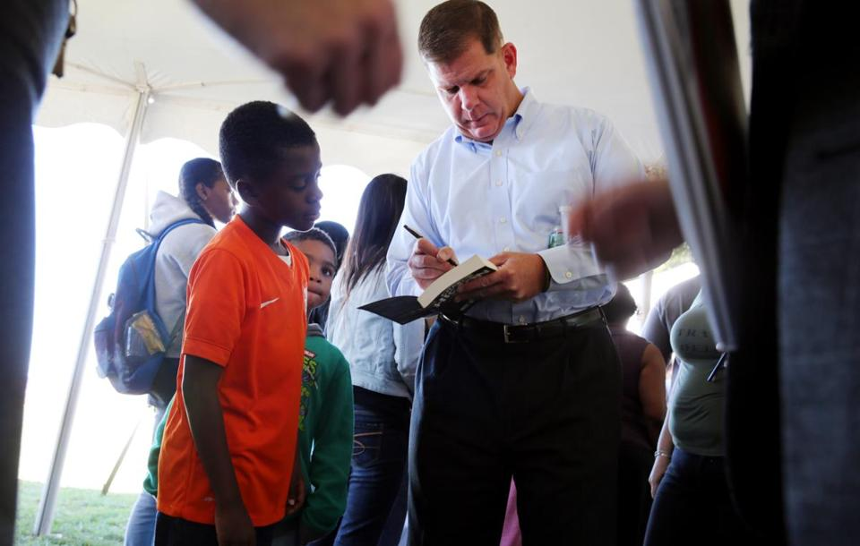 Boston Mayor Martin J. Walsh, who is seeking reelection, signs a book for Galen Buissereth, 10, at a Boston Teachers Union back-to-school fair held Saturday in Dorchester.