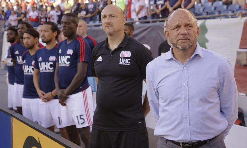 New England Revolution interim head coach Tom Soehn, right, stands with members of his team during the national anthem before an MLS soccer match against Toronto FC, Saturday, Sept. 23, 2017, in Foxborough, Mass. Soehn replaced fired head coach Jay Heaps and is coaching his first game for the Revolution. (AP Photo/Stephan Savoia)