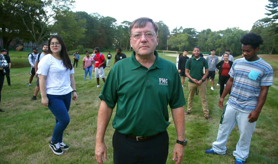 Pine Manor College president Thomas O'Reilly and college students stood on the grounds of their campus. The Town of Brookline has proposed taking the college's land, by eminent domain, to build an elementary school.