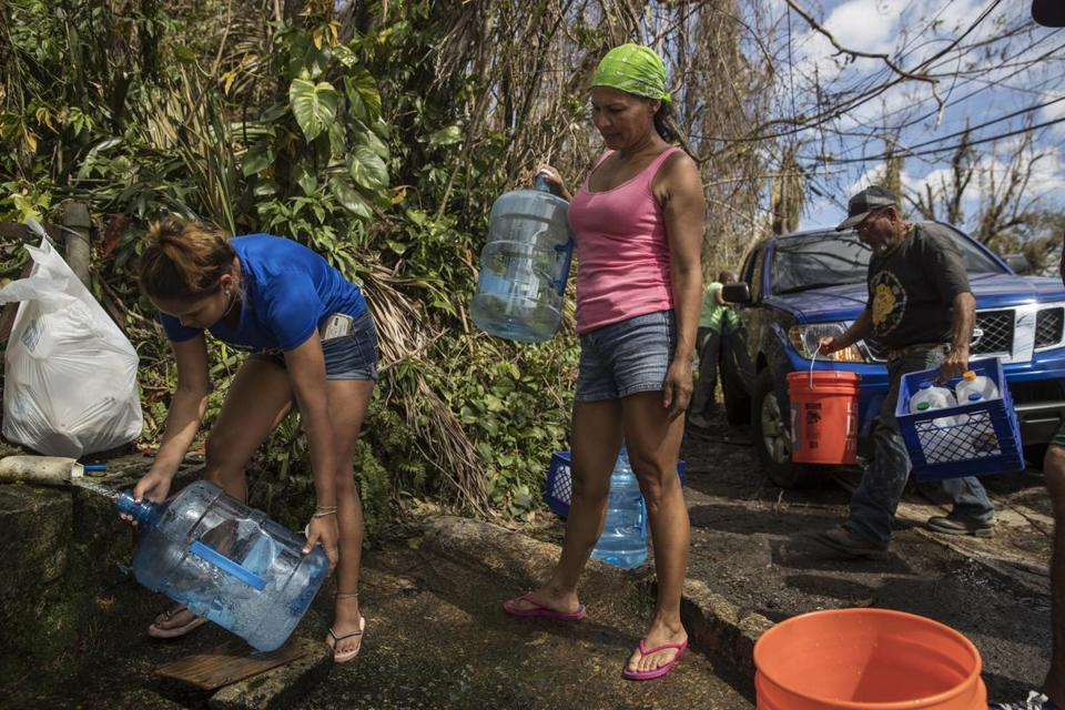 FILE -- Luz Rosado, center, directs the filling of water vessels at a natural spring at her home in Toa Alta, Puerto Rico, Sept. 25, 2017. The Trump administration, which has insisted that its efforts in Puerto Rico were adequate, faced increasing pressure on Sept. 28 to mount a more aggressive response to Hurricane MariaÕs devastating lashing of the island. (Victor J. Blue/The New York Times)