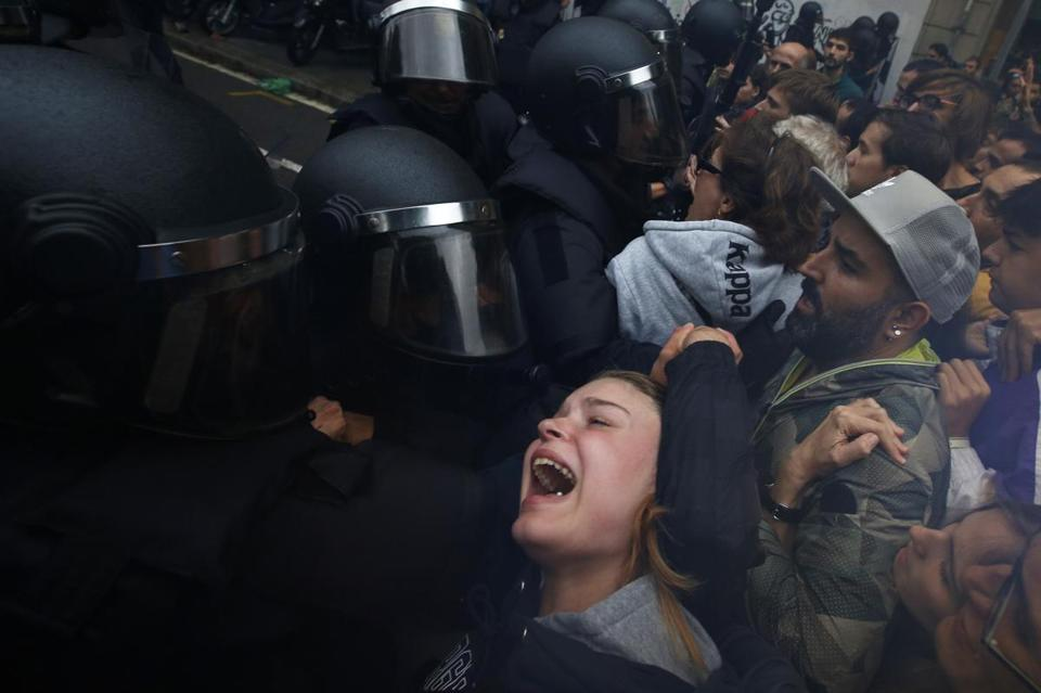 A young woman grimaced as Spanish police pushed away referendum supporters outside a polling station in Barcelona.
