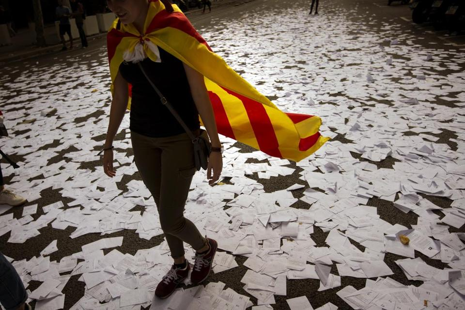 A woman wearing an estelada, or independence flag, walked down a Barcelona street covered with referendum ballots tossed in celebration by pro-independence demonstrators.