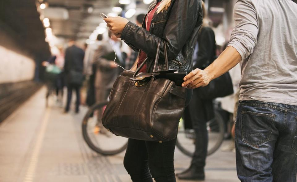 Young woman using mobile phone being robbed by a pickpocket at the subway station. Pickpocketing at subway station