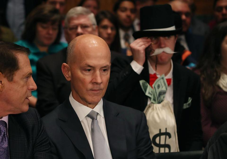 "A protester dressed as the ""Monopoly Man"" sat behind the former CEO of Equifax."