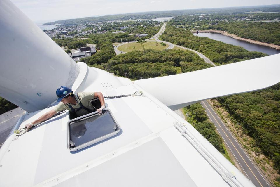 Gloucester, Mass. 6/29/14 Sumul Shah CEO of Solaya Energy secures his safety clips to the top of the wind turbine on Friday, June 27, 2014 at Gloucester's Blackburn Industrial Park. Perched more than 250 feet above ground, the turbines are expected to save the city of Gloucester $11 million in electricity costs over 25 years. (Zack Wittman for the Boston Globe)