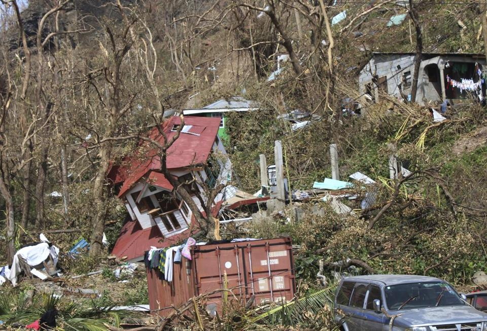 FILE - In this Sept. 23, 2017 file photo, homes lay scattered after the passing of Hurricane Maria in Roseau, the capital of the island of Dominica. Lives have been lost around the Caribbean, including on hard-hit Dominica. A senior U.N. official said Tuesday, Oct. 3, that the recovery of eastern Caribbean islands hardest hit by recent hurricanes could cost up to $1 billion. (AP Photo/Carlisle Jno Baptiste, File)
