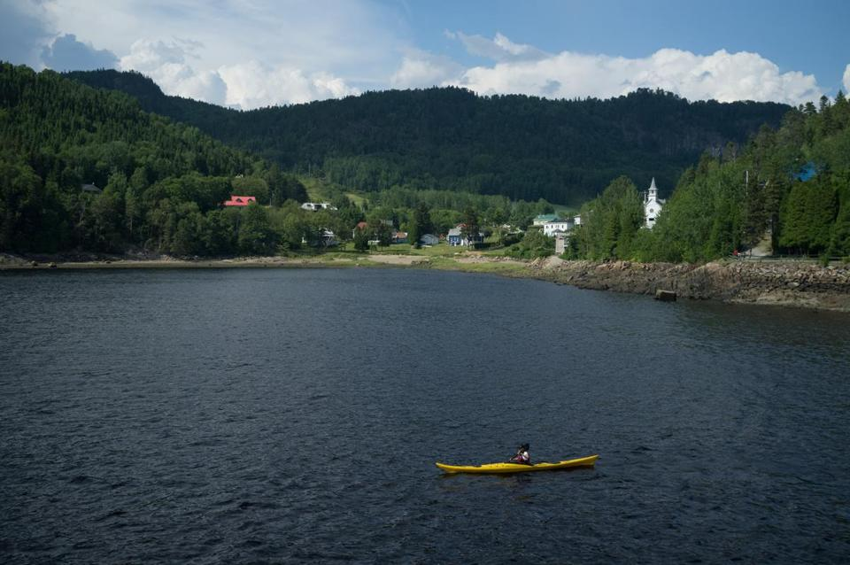 The waters near the Saguenay Fjord offer kayakers amazing views of the Quebec countryside.