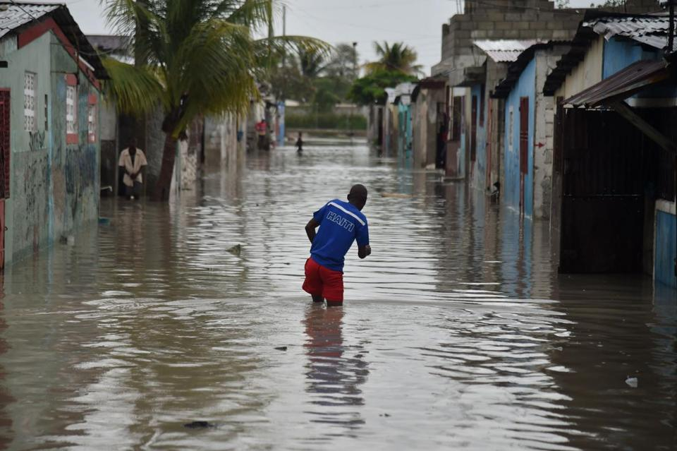 (FILES) This file photo taken on October 4, 2016 shows a man walking in a flooded street, in a neighbourhood of the commune of Cite Soleil, in the Haitian Capital Port-au-Prince. Haiti may have been largely spared from this year's worst hurricanes -- Harvey, Irma and Maria -- but it is still picking up the pieces from disastrous Matthew last year. That hurricane, which struck a year ago to the day, killed more than 500 people and caused two billion dollars in damage in the poorest country in the Americas. And the consquences are not over. The category 4 hurricane was the strongest to hit Haiti in a decade. Still, even though so many people died and so much damage was wrought, it did not change the way the country prepares for natural disasters. / AFP PHOTO / HECTOR RETAMALHECTOR RETAMAL/AFP/Getty Images