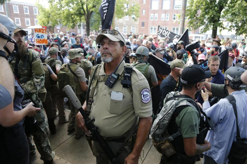 FILE - This Saturday Aug. 12, 2017 file photo, an armed militia member stands guard at a white nationalist rally in Charlottesville, Va. The city of Charlottesville will join a lawsuit that seeks to prevent the heavily armed bands of white nationalists and militia groups that descended on the Virginia city for a violent summer rally from returning. The City Council held a special meeting Thursday, Oct. 12, where they voted to join the lawsuit. (AP Photo/Steve Helber)