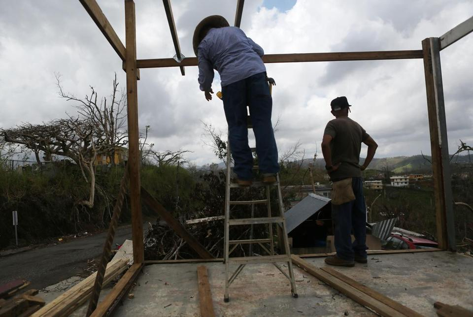 Men work Wednesday to repair a partially destroyed bar three weeks after Hurricane Maria hit the island.