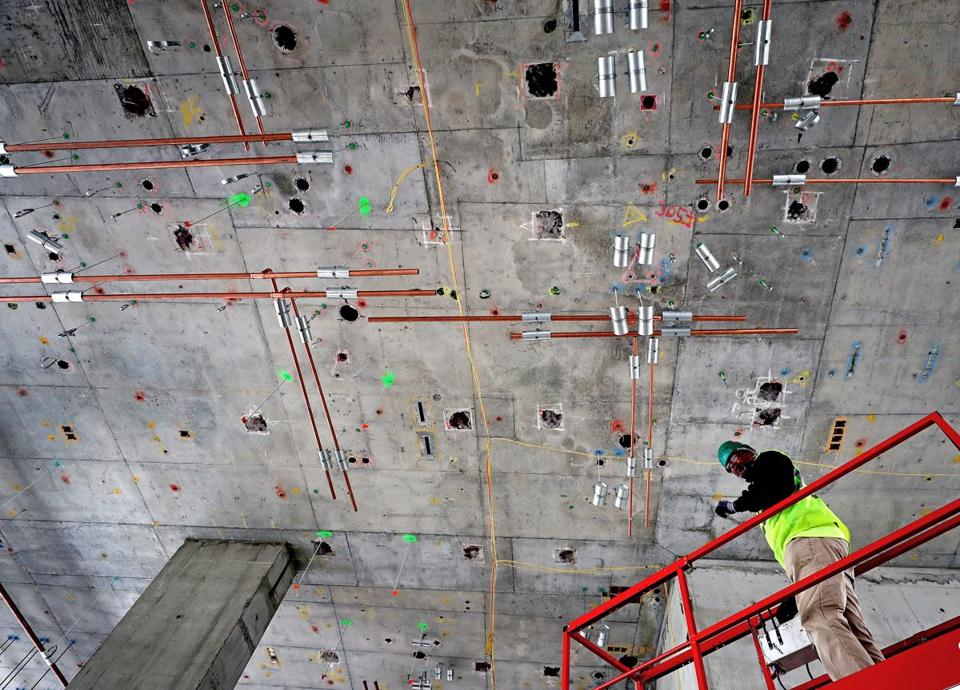 EVERETT, MA - 10/16/2017: Ronald Lawrence a plumber works above on pipe work that is attached to the ceiling at Wynn casino in Everett that is a work in progress. (David L Ryan/Globe Staff ) SECTION: METRO TOPIC 17wynnbuild