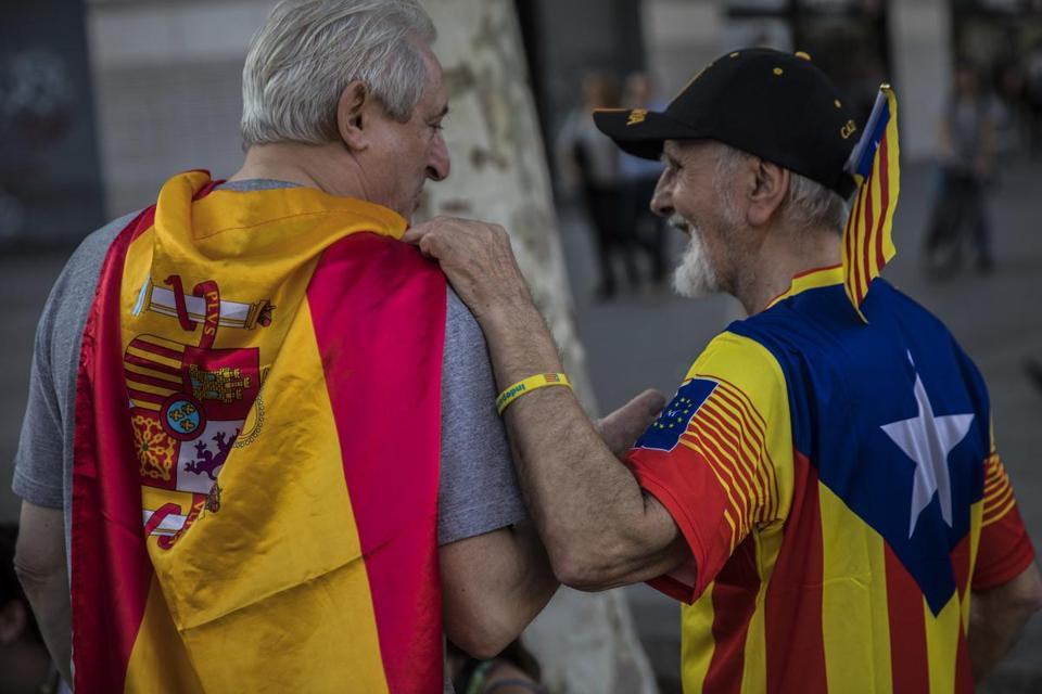 Two men, one wearing a Spanish flag (left) and the other an independence flag, talked in Barcelona on National Day.