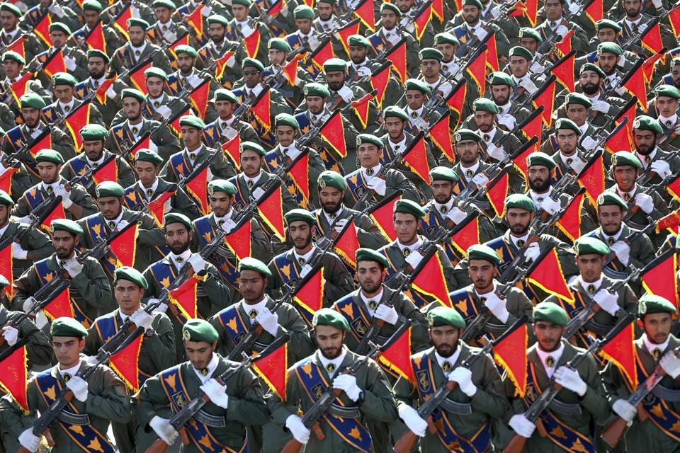 FILE - In this Sept. 21, 2016 file photo, Iran's Revolutionary Guard troops march in a military parade marking the 36th anniversary of Iraq's 1980 invasion of Iran, in front of the shrine of late revolutionary founder Ayatollah Khomeini, just outside Tehran, Iran. While U.S. President Donald Trump angered Iran with his speech on refusing to re-certify the nuclear deal, Tehran won't walk away from it in retaliation. (AP Photo/Ebrahim Noroozi, File)