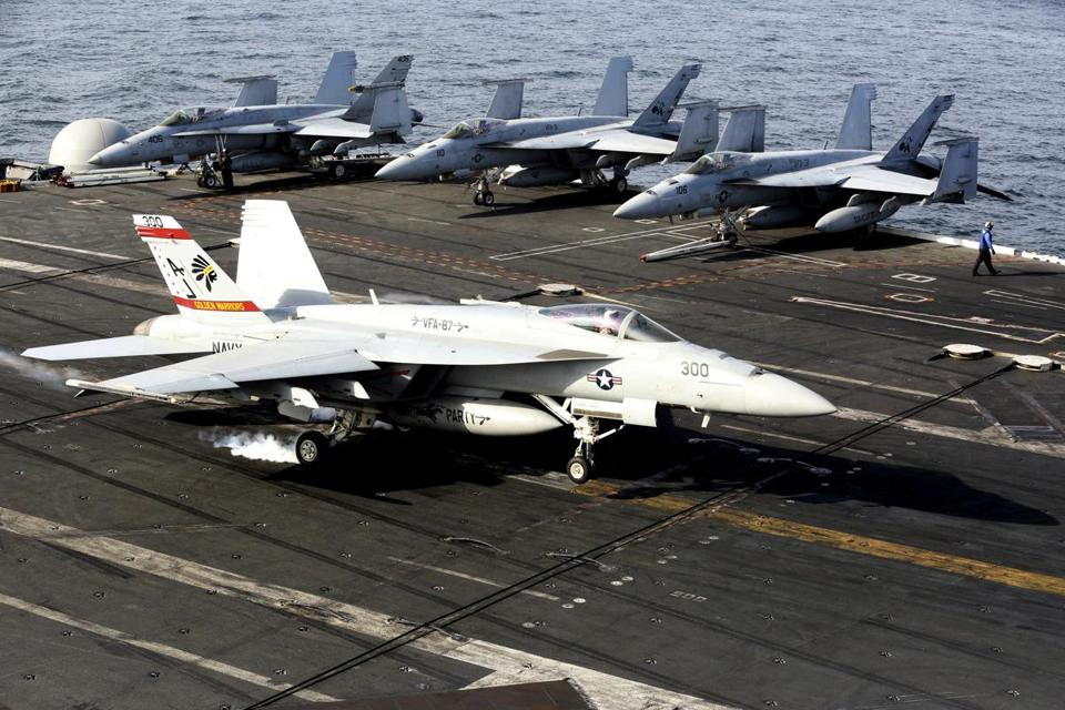 FILE - In this March 20, 2017 file photo, an F-18 fighter jet lands on the USS George H.W. Bush as it travels toward the Strait of Hormuz. While U.S. President Donald Trump angered Iran with his speech on refusing to re-certify the nuclear deal, Tehran won't walk away from it in retaliation. (AP Photo/Jon Gambrell, File)