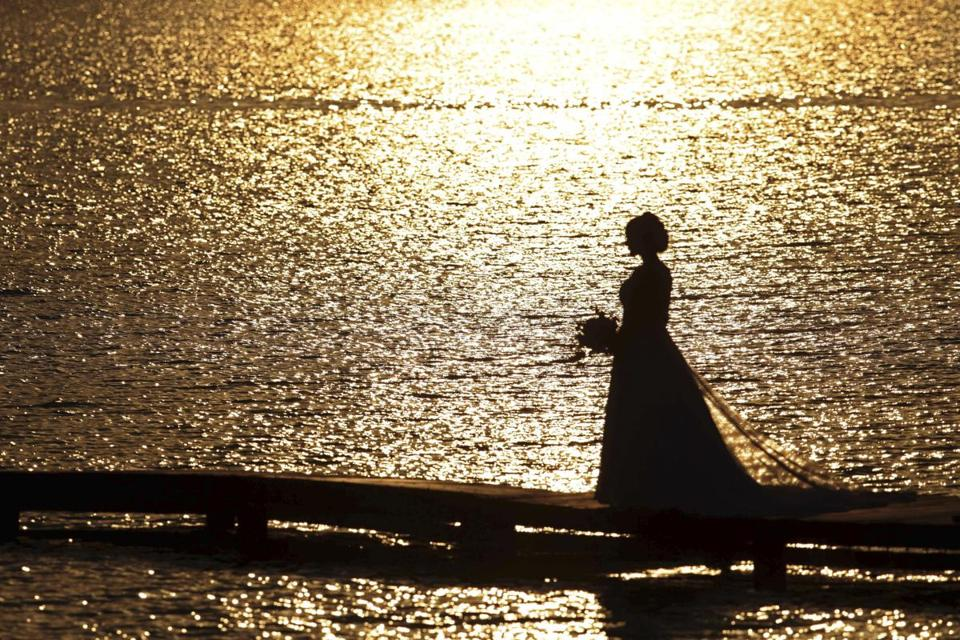A bride poses for her wedding pictures on a pier along the shore of Lake Paranoa, on the 100th day without rain in Brasilia, Brazil, Wednesday, Aug. 30, 2017. The capital's drought record occurred in 1963, when the capital was without rain for 164 days, or about five months. (AP Photo/Eraldo Peres)