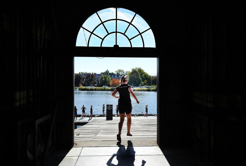 A crewmember of an Alumnae Women's Eight boat ran to the dock through the door of the Weld Boathouse on Saturday.