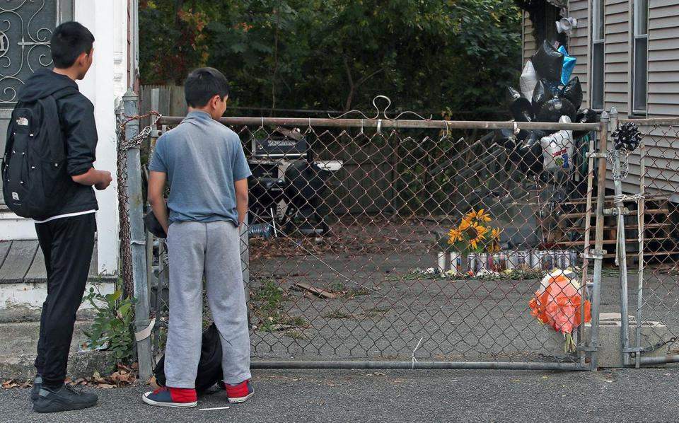 Neighborhood children looked at the memorial to the 7-year-old boy who was mauled to death Saturday in Lowell.