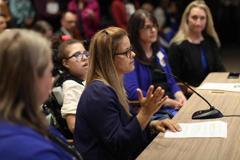 Noelia Ferreira (center) spoke at the State House on Tuesday in support of a bill that would help families that use the state's home nursing program.
