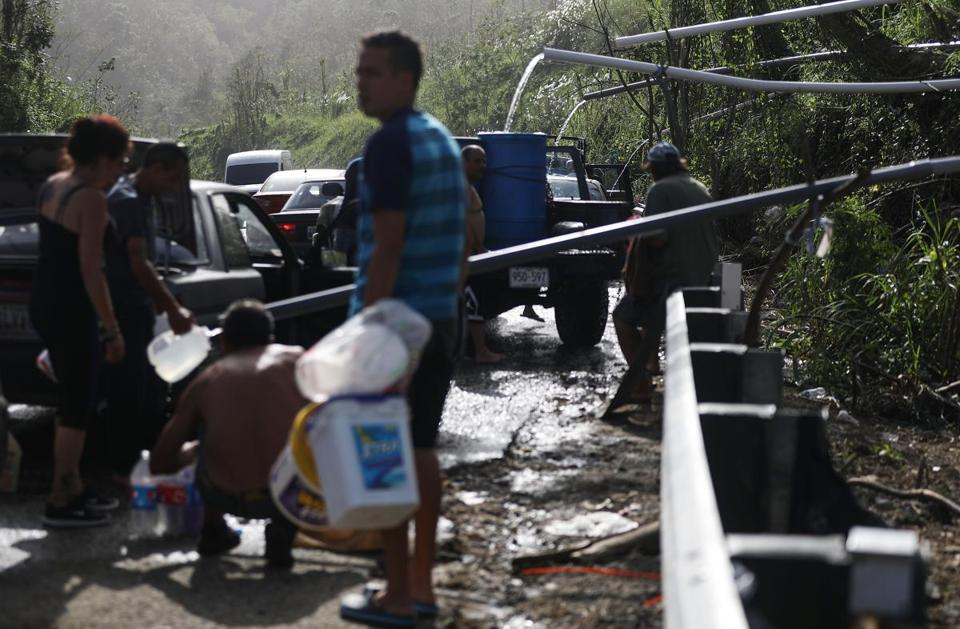 UTUADO, PUERTO RICO - OCTOBER 19: People fill containers with water funneled with pipes from a mountain stream nearly one month after Hurricane Maria struck on October 19, 2017 in Utuado, Puerto Rico. Puerto Rico is suffering shortages of food and water in areas with only 21.6 percent of grid electricity and 71.58 percent of running water restored. Puerto Rico experienced widespread damage including most of the electrical, gas and water grid as well as agriculture after Hurricane Maria, a category 4 hurricane, swept through. (Photo by Mario Tama/Getty Images)