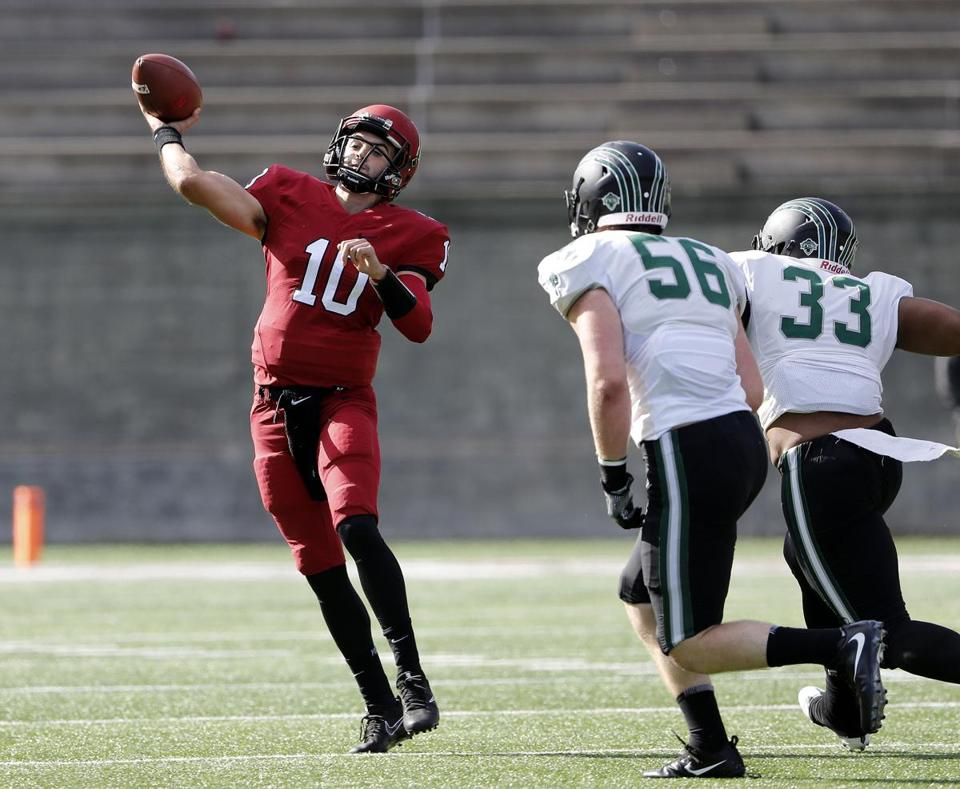 Harvard Crimson quarterback Jake Smith throws under pressure from Dartmouth Big Green linebacker Eric Meile (56) and linebacker Justin Edwards during their football game at Harvard Stadium in Allston, Mass., Saturday, Oct. 28, 2017. (Winslow Townson for The Boston Globe)