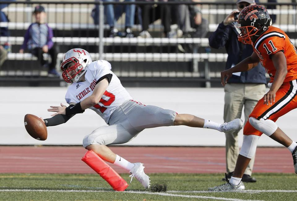 Catholic Memorial's Nick Goffredo dives for the end zone but comes up just short as Newton North's Will Thompson looks on during their football game in Newton, Mass., Saturday, Oct. 28, 2017. (Winslow Townson for The Boston Globe)