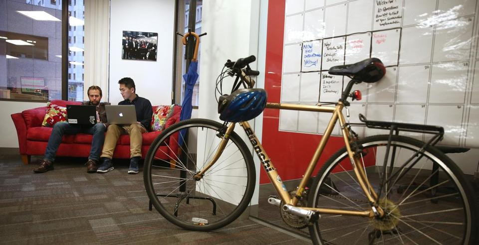 Boston, MA - 10/16/2017 - TPTW Tech consultants Sean Duhaime (cq), left, and Max Lim (cq) work on developing customer requirements. The bike belongs to CEO Ellen Daley (cq). The 4-year-old Acorio (cq) is the winning small company. (Pat Greenhouse/Globe Staff) Topic: 111917small-Acorio Reporter: Sarah Shemkus