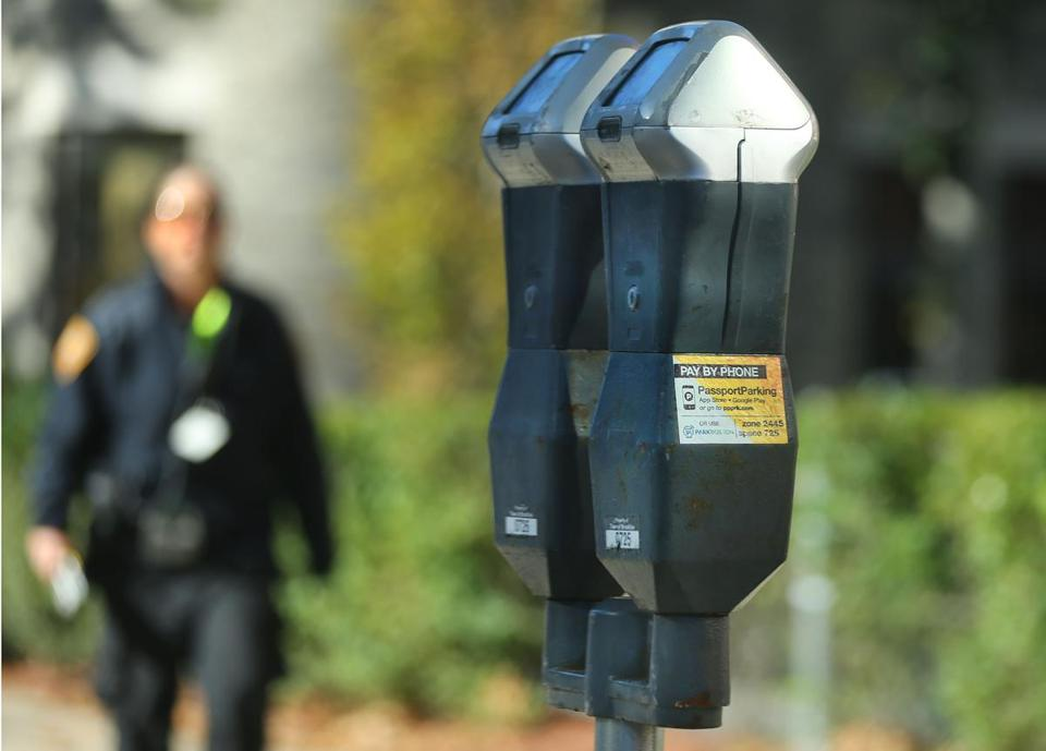 A Brookline parking enforcement officer approached a meter.