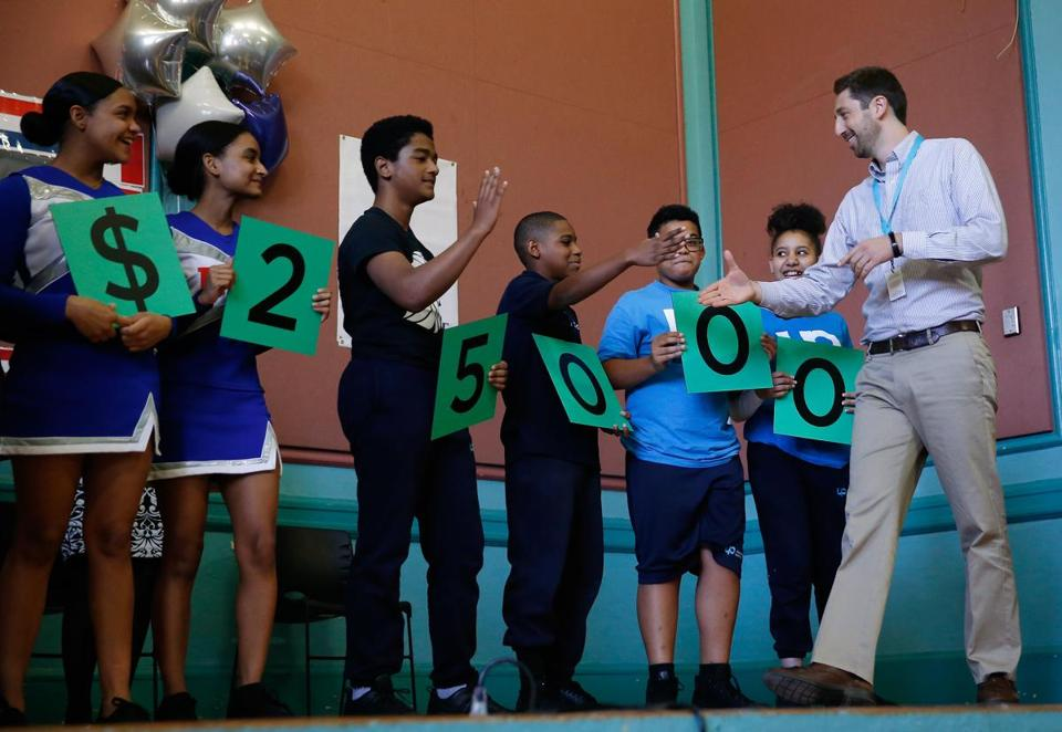 Daniel Adler, a sixth grade Science teacher at Up Academy Leonard, in Lawrence shook hands with students as he took the stage after being named the recipient of the $25,000 Milken Award.