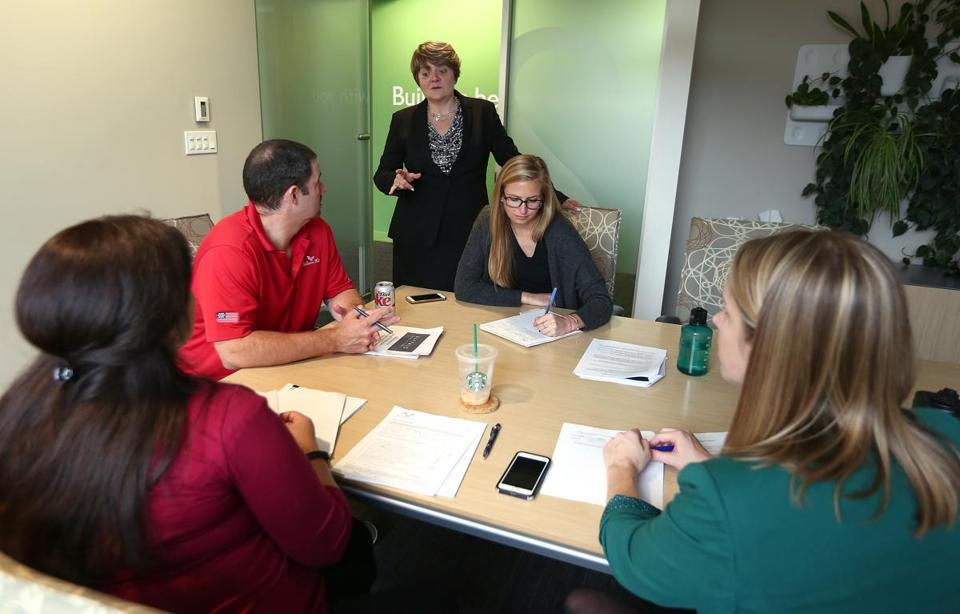 Boston, MA - 10/24/2017 - TPTW Lisa Brothers (cq), standing, drops in on a go/no-go meeting for responding to a project proposal. Seated clockwise from left are Anna Luciano (cq), Scott Turner (cq), Virginia Steigerwald (cq), and Jennifer Johnson (cq). Brothers is chairman and CEO of Nitsch Engineering (cq). (Pat Greenhouse/Globe Staff) Topic: 111917wagegap Reporter: Stephanie Ebbert