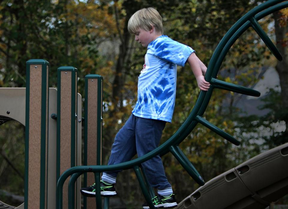 Wenham, MA - 11/02/17 - Leo Woolfenden (cq) plays on a structure during recess at the Bessie Buker Elementary School. Left with struggles after the Marathon Bombing, his classmates have helped him without even knowing what happened to him and his family. (Lane Turner/Globe Staff) Reporter: (Billy Baker) Topic: (05monkeybars) Monkey Bars