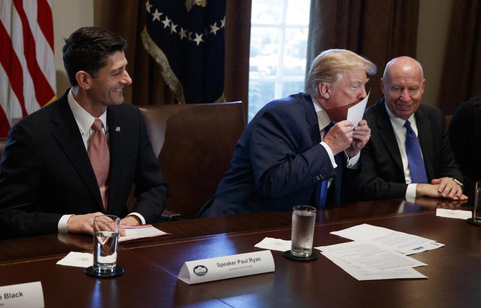 President Donald Trump kisses a printed example of what a new tax form may look like during a meeting on tax policy with Republican lawmakers in the Cabinet Room of the White House, Thursday, Nov. 2, 2017, in Washington, as House Speaker Paul Ryan of Wis., and chairman of the House Ways and Means Committee Rep. Kevin Brady, R-Texas, watch. (AP Photo/Evan Vucci)