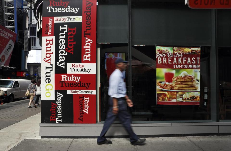 In this Friday, Sept. 16, 2016, photo, a man walks by a Ruby Tuesday restaurant in New York's Times Square. Ruby Tuesday is being bought by private-equity firm NRD Capital, in a deal that will take the struggling restaurant chain private. Like other sit-down restaurant chains, Ruby Tuesday has had a hard time attracting diners who are increasingly eating at cheaper, faster and more casual places. (AP Photo/Mary Altaffer)