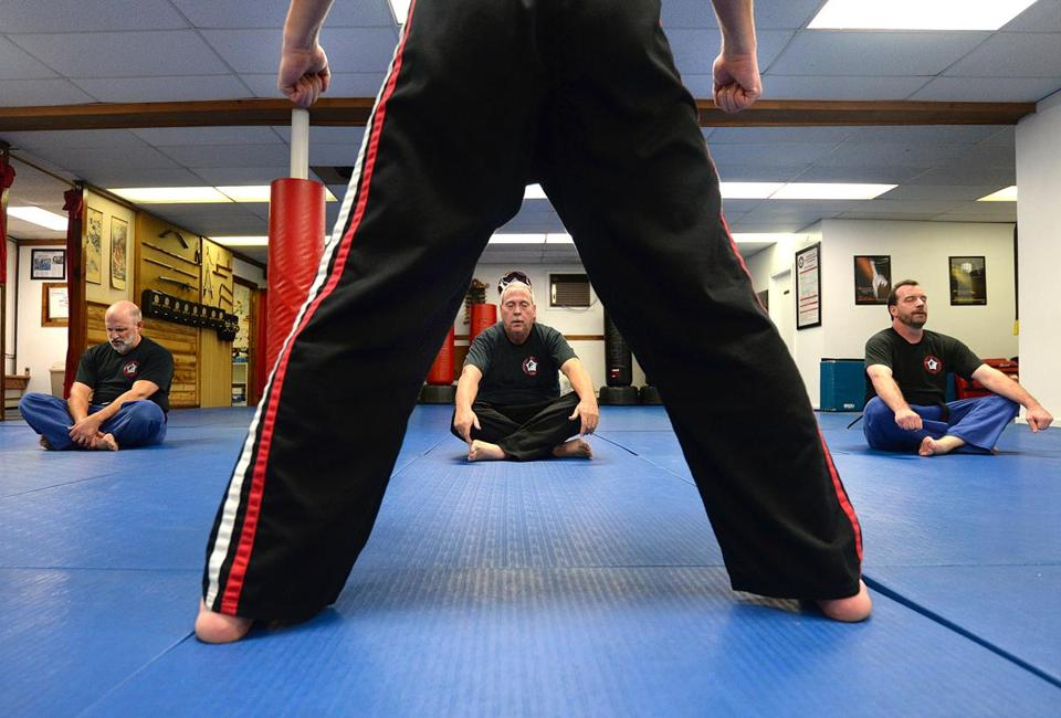 Weymouth 11/02/2017: (l-r) Victor DeRubeis (cq) of Weymouth age 61, Brian Finnerty of Weymouth, 59, and Jay Krim of Rockland 49, meditate after their Martial Arts class that was instructed by Chuck Anderson (forground) at the American Kempo Karate Academy in Weymouth. Photo by Debee Tlumacki for the Boston Globe (south)
